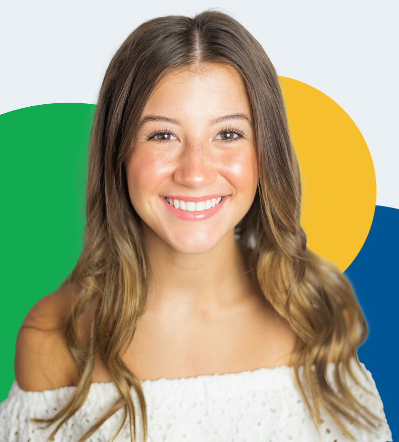 Photo of a patient, smiling at the camera to show her smile after undergoing orthodontic treatment.